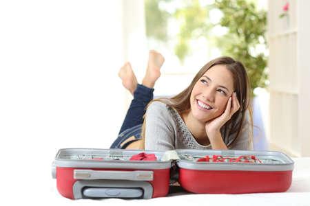 mujer con maleta: Mujer feliz pensando y preparando un viaje acostado en una cama en su casa u hotel