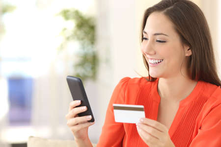 happy customer: Lady buying online with a credit card and smart phone sitting on a couch at home with a blurred background Stock Photo