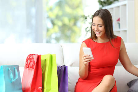 Woman in red using a smart phone with shopping bags beside