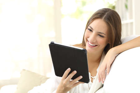 e pretty: Happy woman reading an ebook or tablet sitting on a couch at home Stock Photo