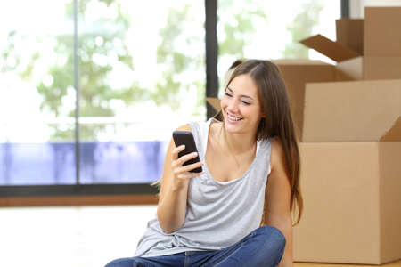 e pretty: Happy woman moving home texting in a smart phone sitting on the floor Stock Photo