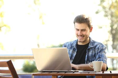 起業家男レストラン テラスまたは自宅バルコニーでノート パソコンでの作業