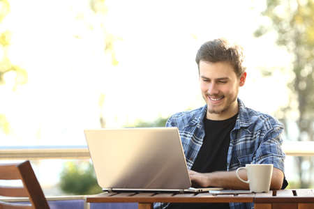 Imprenditore uomo che lavora con un computer portatile in un ristorante con terrazza o balcone di casa Archivio Fotografico