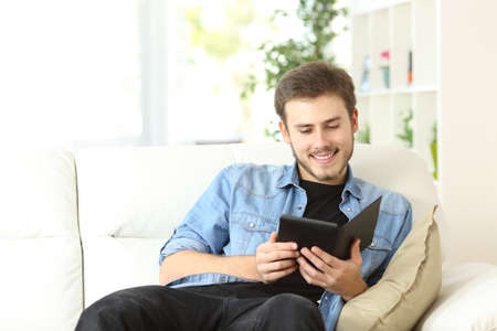 ebook: Happy man reading a book in an ebook reader sitting on a couch at home