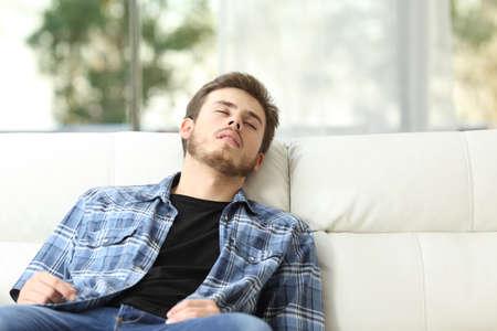 自宅のソファで寝ている疲れた男の正面図 写真素材
