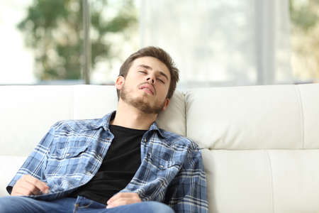 young man: Front view of a tired man sleeping on a couch at home Stock Photo