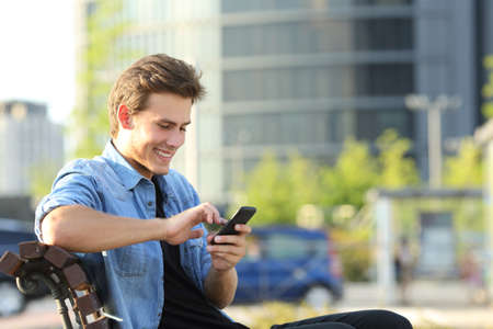 typing man: Entrepreneur working texting in a mobile phone sitting on a bench with office buildings in the background Stock Photo