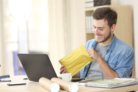 INVOICE: Entrepreneur opening a padded envelope in a little office or home