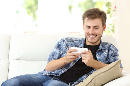 Man playing online games with a smart phone sitting on a couch at home Banco de Imagens