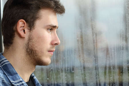 pensive man: Side view of a man longing and looking through window in a sad rainy day Stock Photo