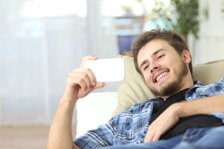 Hombre feliz viendo películas en un teléfono inteligente acostado en un sofá en casa Foto de archivo