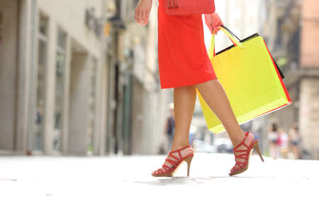 woman bag: Side view of a shopper woman legs walking with shopping bags in a commercial street