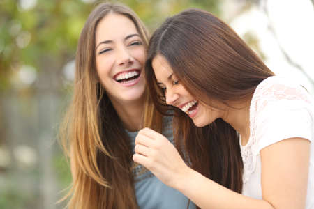 Two happy woman friends laughing together in a park with a green background