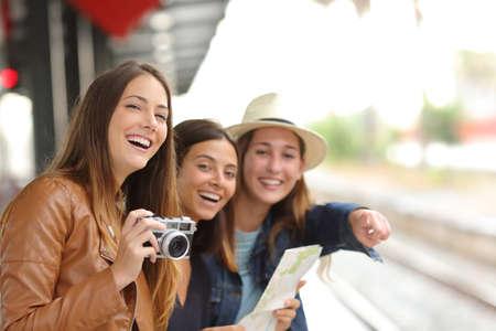 Grupp av tre resenärer flickor resa och väntar på en järnvägsstation plattform