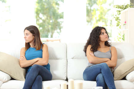 other side of: Two angry friends after a quarrel sitting on a couch and looking at the other side Stock Photo