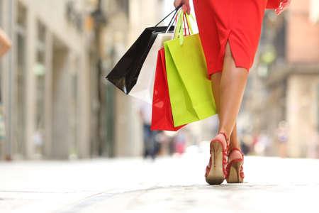 通りでカラフルなショッピング バッグと歩いてファッション ショッパー女性足の背面します。