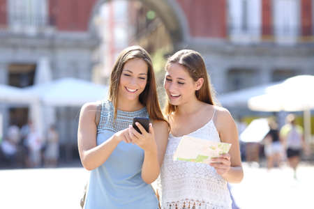 tourist tourists: Two tourist friends consulting an online guide on a smart phone in the street