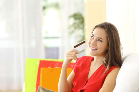 shopping card: Woman thinking with credit card sitting on a couch with shopping bags at home