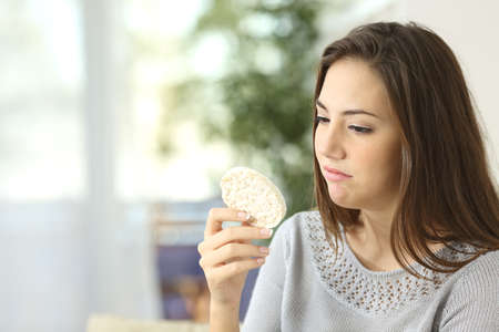 insipid: Girl disgusted looking a dietetic cookie. Bad diet concept Stock Photo