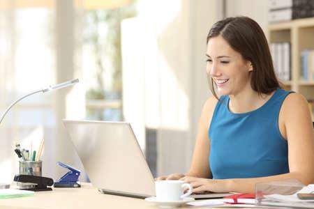 empresario ocasional feliz que trabaja en la tipificación de línea con un ordenador portátil en la oficina con una ventana en el fondo Foto de archivo