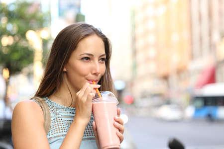 alimentos y bebidas: Pensativo mujer feliz bebiendo un batido en la calle