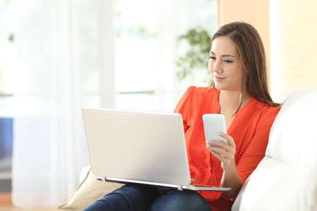 Imprenditore donna che lavora con un computer portatile e telefono cellulare seduto su un divano a casa Archivio Fotografico