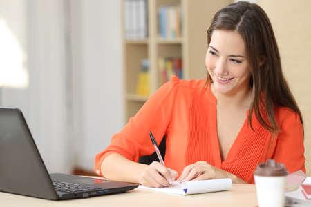 Empresario que trabaja en línea con un ordenador portátil y tomando notas en un bloc de notas en un pequeño escritorio de oficina o el hogar Foto de archivo