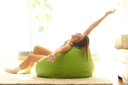 pouf: Happy girl stretching arms looking at camera and sitting on a pouf at home
