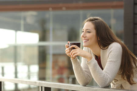 Retrato de una mujer de pensamiento feliz y mirando a otro lado en el desayuno de vacaciones con un complejo o un hotel en la playa en el fondo