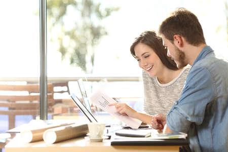 Grupo de dos compañeros de trabajo comparando los gráficos de predicción en una cafetería con una ventana en el fondo Foto de archivo