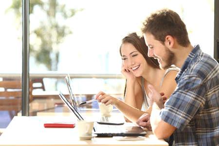 Zijaanzicht van twee jonge volwassen studenten studeren en praten over de lessen elkaar vergelijken laptop informatie in een coffeeshop