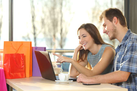 Couple of shoppers with shopping bags buying online and choosing products in a coffee shop