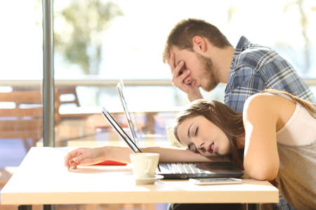 Vista lateral de los estudiantes cansados ??de entregarse a la fatiga estudio con ordenadores portátiles en una cafetería con una ventana en el fondo y el cielo al aire libre