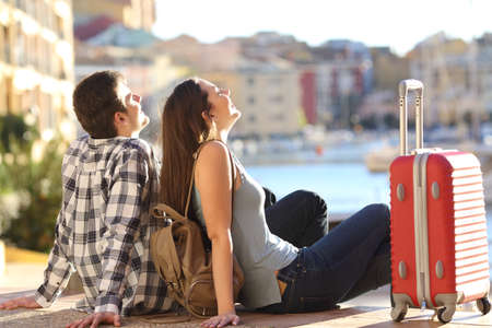 Side view of a couple of 2 tourists with a suitcase sitting relaxing and enjoying vacations in a colorful promenade. Tourism concept