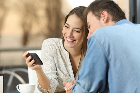 Happy casual couple laughing and watching together streaming videos on line in a generic smart phone dating in a bar with a warm sunset outdoor in the background