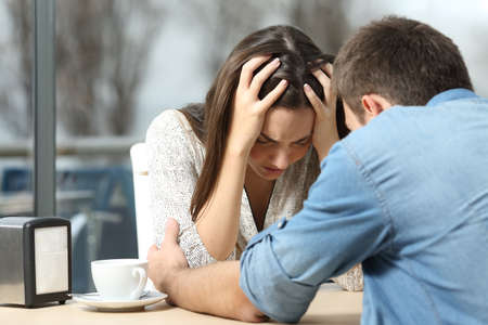 angry people: Male comforting to a sad depressed female who needs help in a coffee shop. Break up or best friend concept