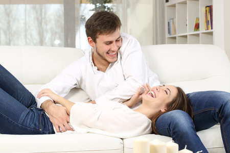 Playful couple or marriage tickling and laughing in a couch at home Stock Photo