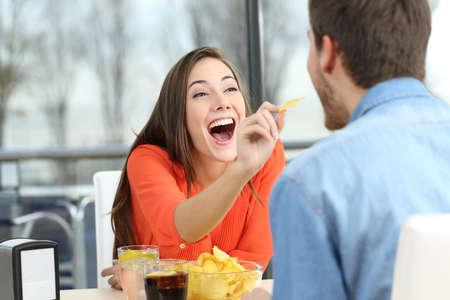 botanas: Pareja juguetona comiendo patatas chips y bromeando mirando uno al otro en una fecha en una cafetería