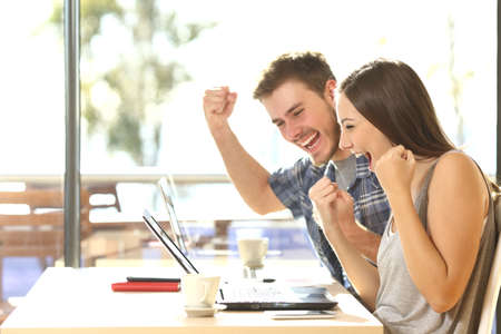 reir: Grupo de dos jóvenes estudiantes de euforia viendo los resultados del examen en un ordenador portátil en una mesa de un bar campus universitario