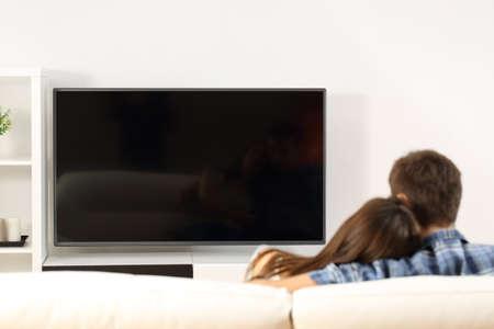 Zadní pohled na pár televizi v gauči doma. Prázdný pohled na displej