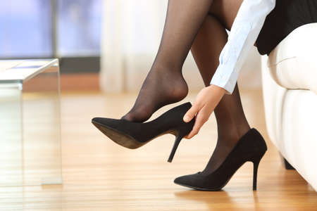 Businesswoman taking off high heels shoes after work at home Stock Photo