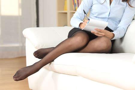 Podnikatelka nohy s punčochy odpočívá doma a psaní poznámek Reklamní fotografie