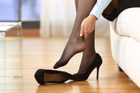 piernas con tacones: Empresaria cansada con dolor de articulaciones tocar su tobillo sentado en un sofá en casa