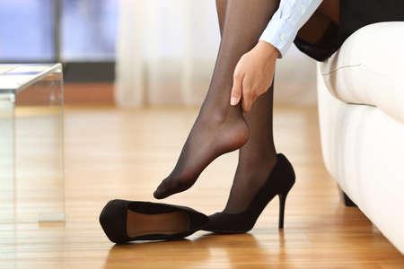 Müde Geschäftsfrau mit Gelenkschmerzen ihren Knöchel berührt auf einer Couch zu Hause sitzen Lizenzfreie Bilder