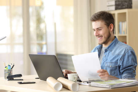 Entrepreneur working with a laptop and holding a document in a little office or home Banco de Imagens