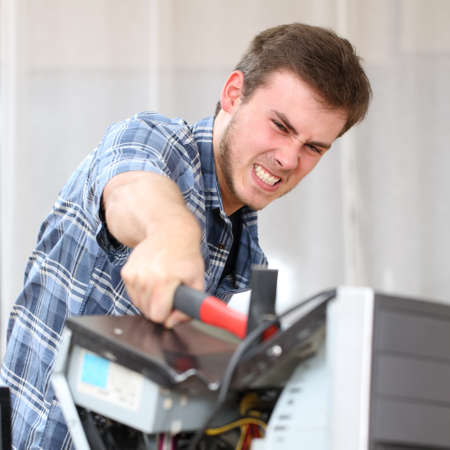out of control: Portrait of furious and crazy man without self control hitting a computer with a hammer hating technology problems in office or home