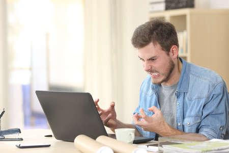 Empresario enojado y furioso con un ordenador portátil en una pequeña oficina o el hogar