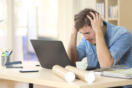 Sad freelance male worried watching bad news on line with a laptop on a desk at home or a little office Zdjęcie Seryjne - 59038869