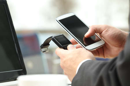 synchronizing: Close up of a professional businessman hands working on line and synchronizing a modern generic smart watch beside mobile phone in a bar