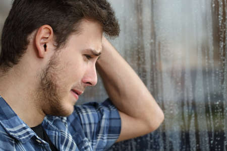 Vue de côté d'un homme triste regardant par la fenêtre presque pleurer dans un jour de pluie